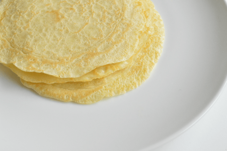 A stack of 3 golden yellow and thin crepes.