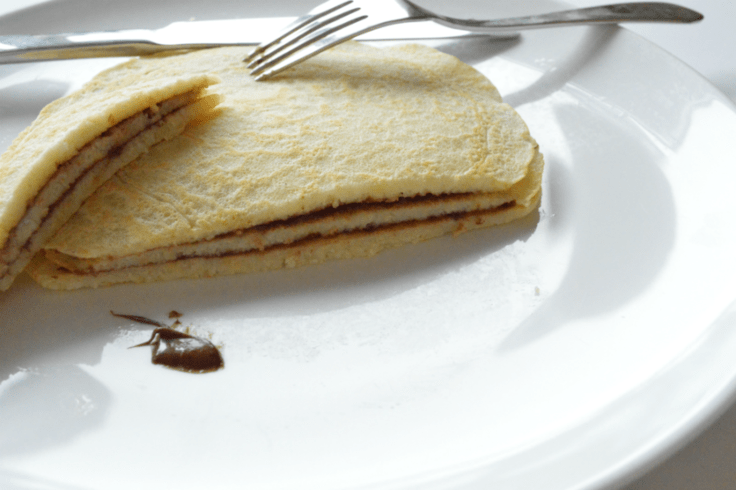 Stack of crepes on a plate with layers of Nutella between each one.
