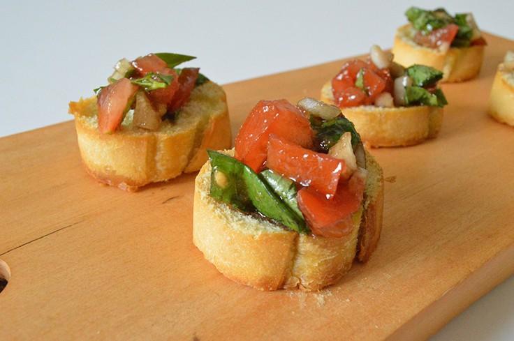Tomato basil bruschetta on a wooden cutting board.