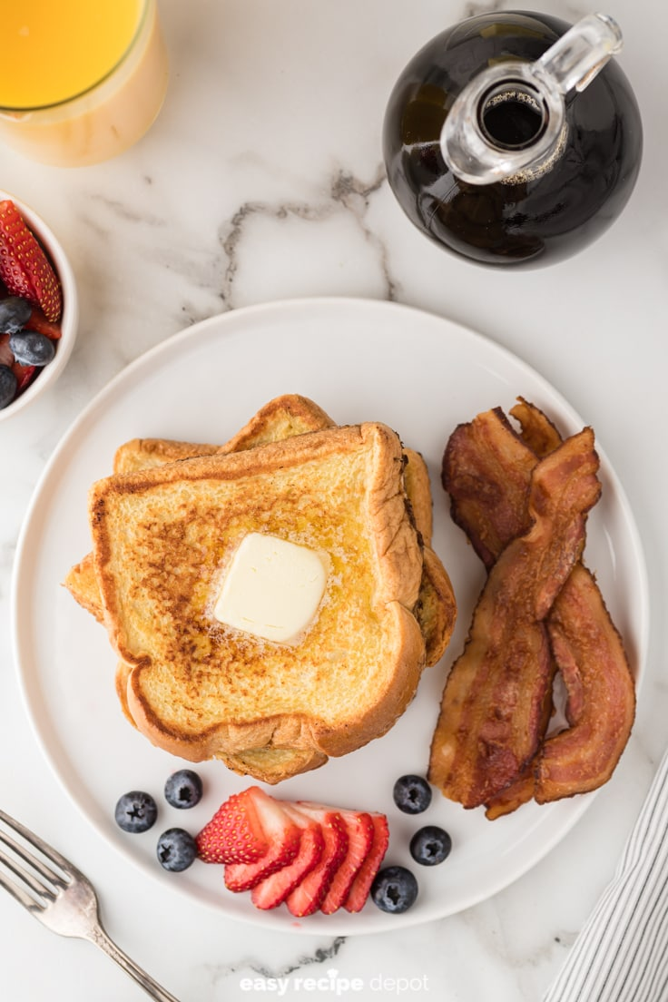 Stack of french toast with butter, bacon, and fruit.