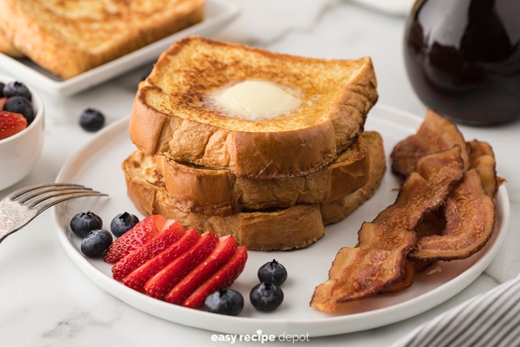 French toast served with fruit and bacon.