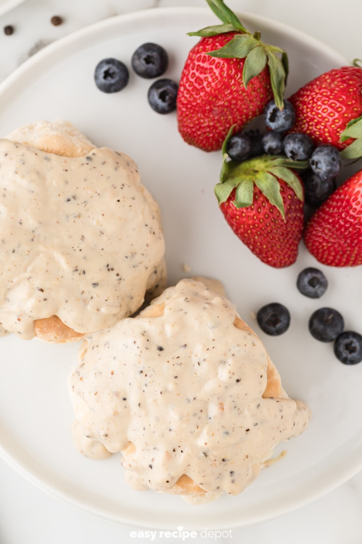 Biscuits and black pepper gravy served with fruit.