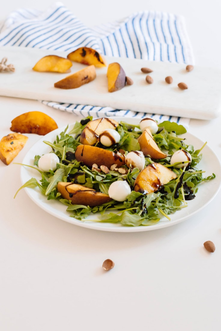 Arugula and grilled peach summer salad on a white dinner plate with dressing.