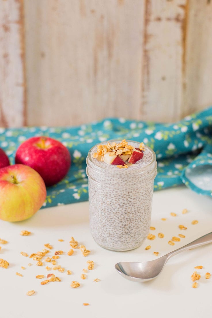 A jar of chia pudding beside a spoon and a few whole apples.
