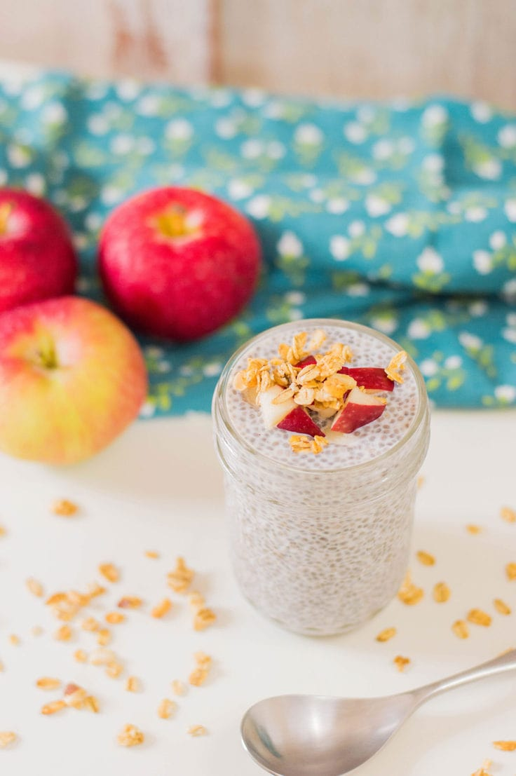 Chia pudding in a mason jar topped with granola and diced apple.