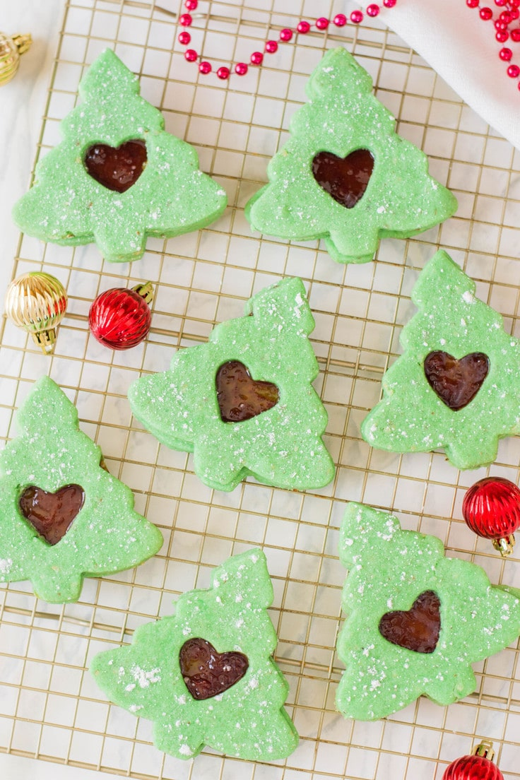Chistmas tree Linzer cookies to add a festive touch to your holiday sweet table. Everything about the Linzer cookies are homemade - from the almond flour down to the jam! #linzercookies