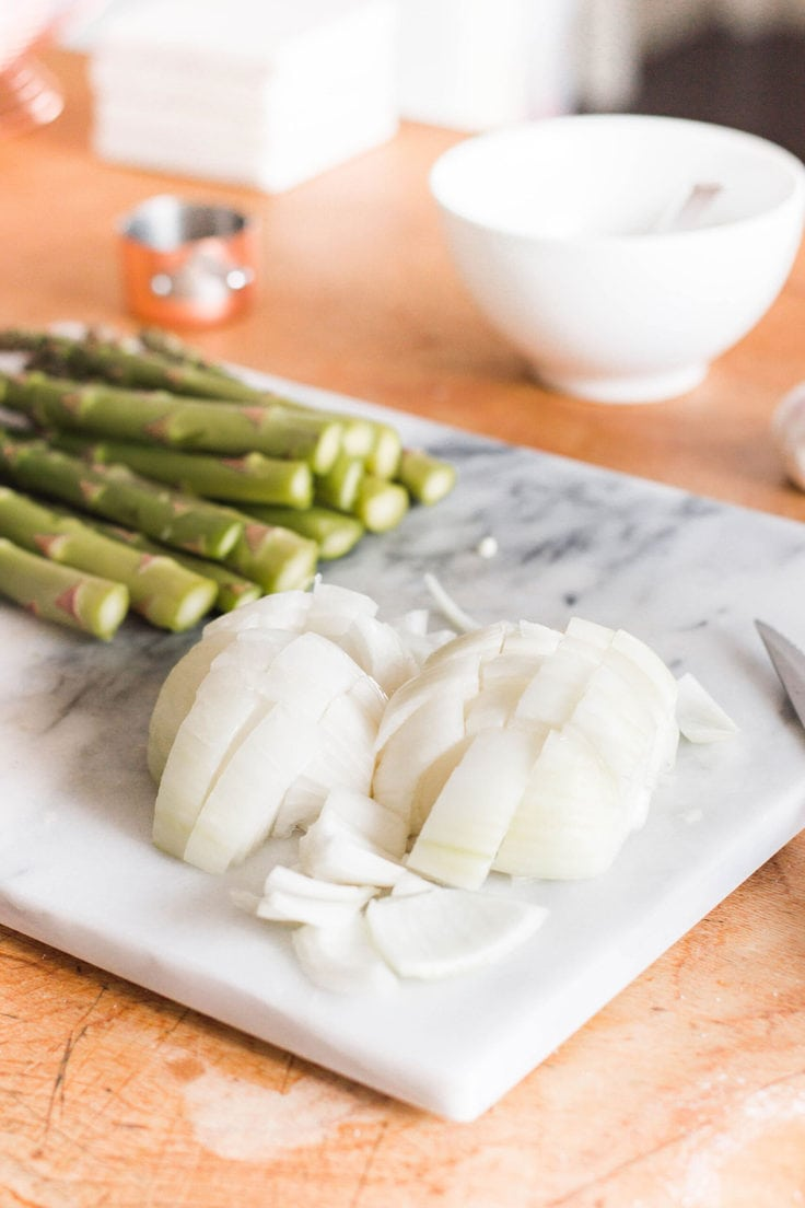 Diced white onion and asparagus on a cutting board.