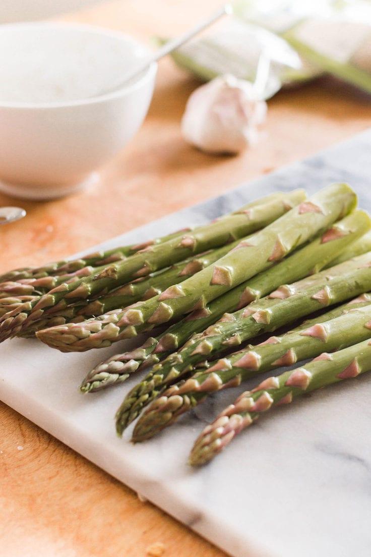 Asparagus stems on a cutting board.