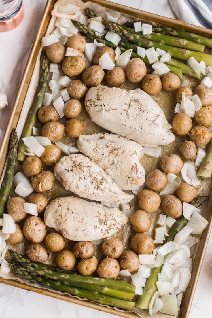 Chicken breasts on a baking sheet surrounded by potatoes, onions, and asparagus.