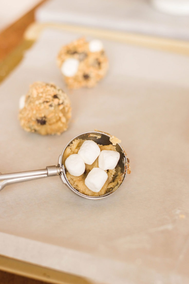 Graham crackers, marshmallows and extra chocolate chips come together to form these decadent S'mores Cookies. Learn how to make a batch of your very own!