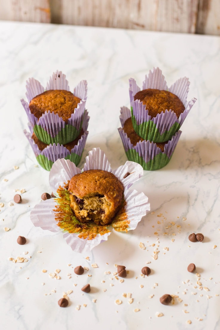 Muffins in green and purple flower shaped wrappers.