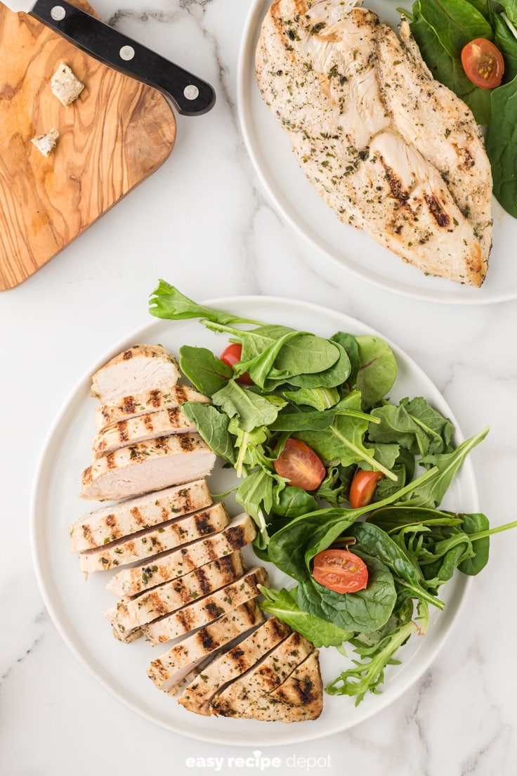 Low-sodium chicken breasts sliced on a plate and served with salad of greens and tomatoes.