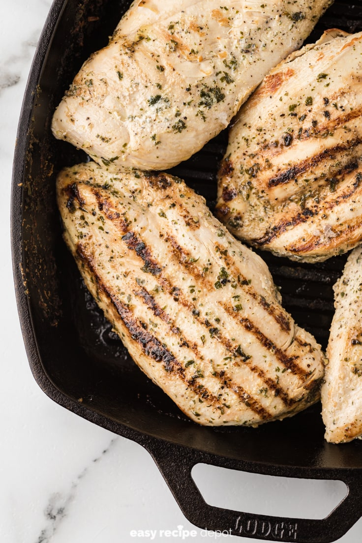 Seasoned low-sodium chicken breasts in a cast iron grill pan.