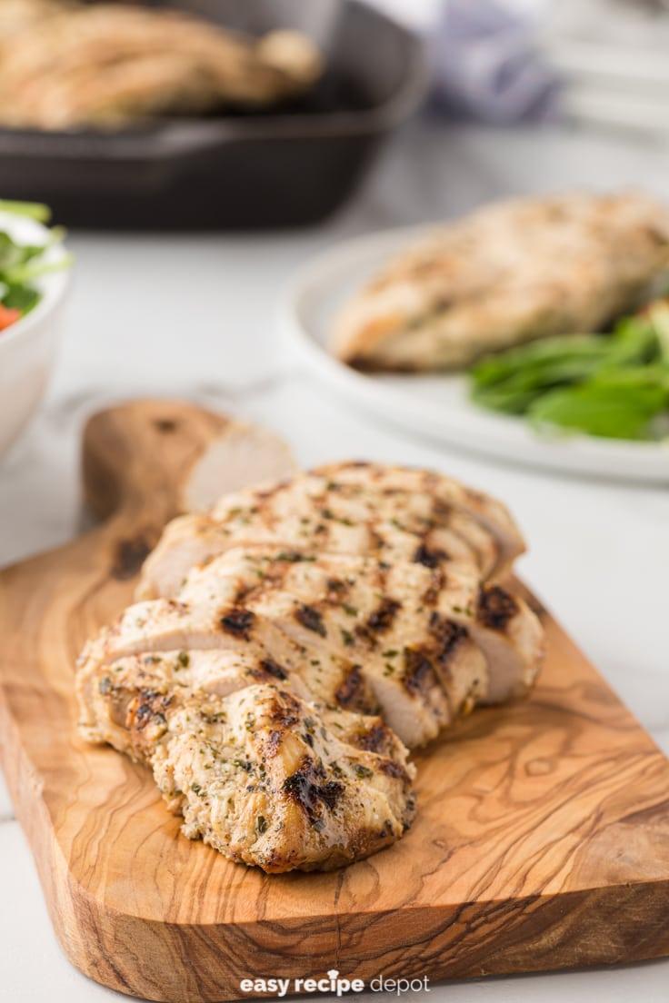 Boneless, skinless chicken breast sliced on a cutting board.