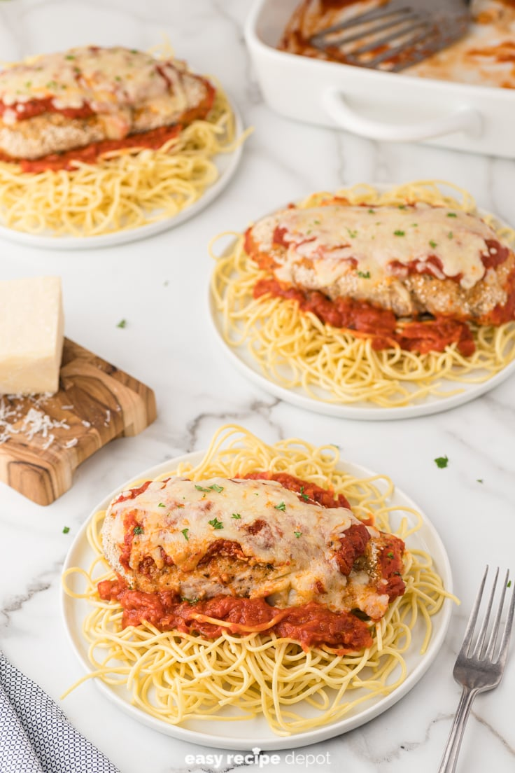 Spaghetti topped with tomato sauce and chicken parmesan.