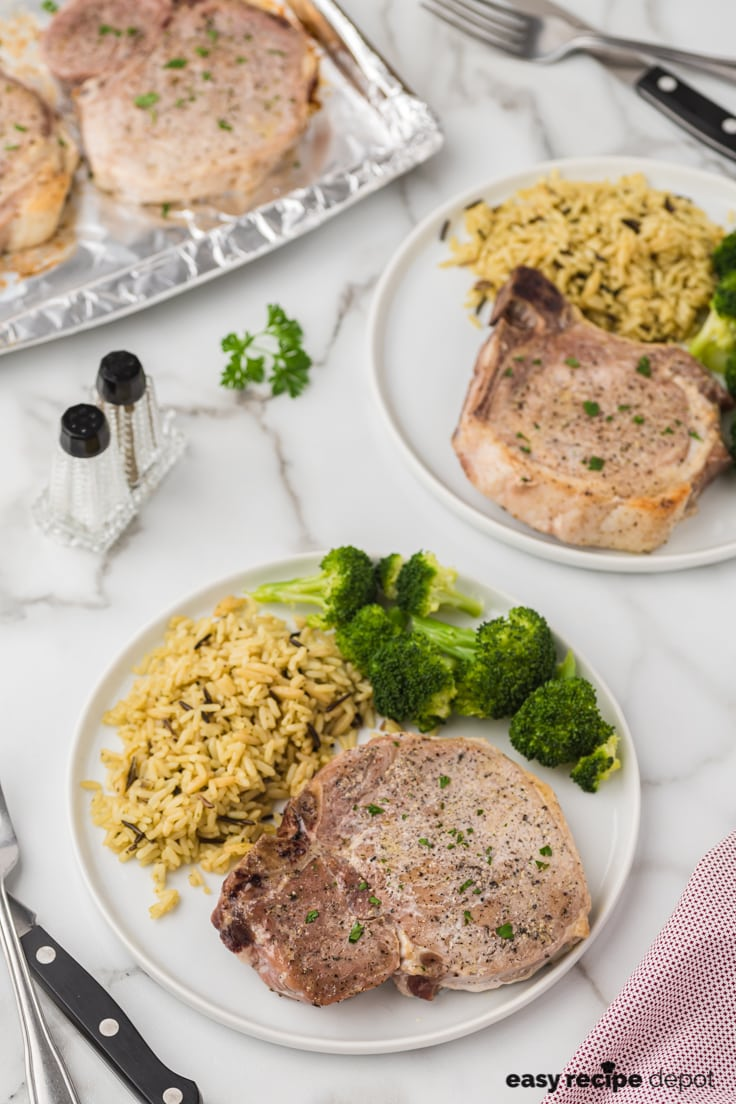 Baked pork chops served on a plate with sides of broccoli and rice.