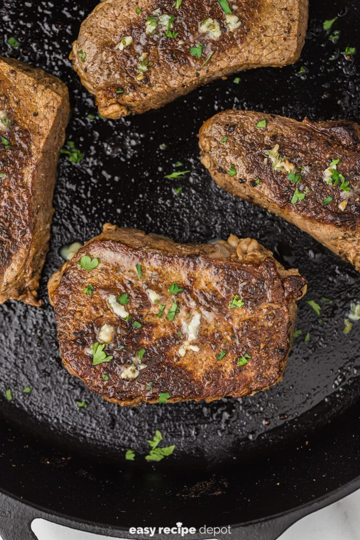 Pan seared steak in a cast iron skillet on stove.