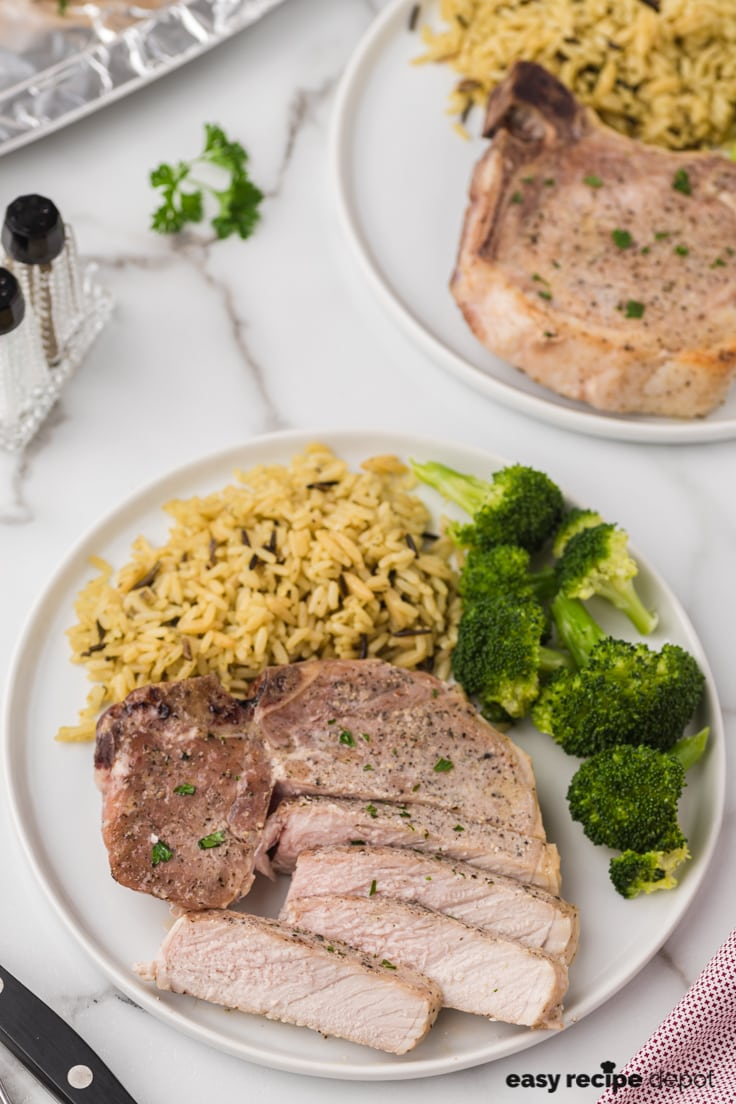 A dinner plate with a sliced pork chop, seasoned rice, and steamed broccoli.