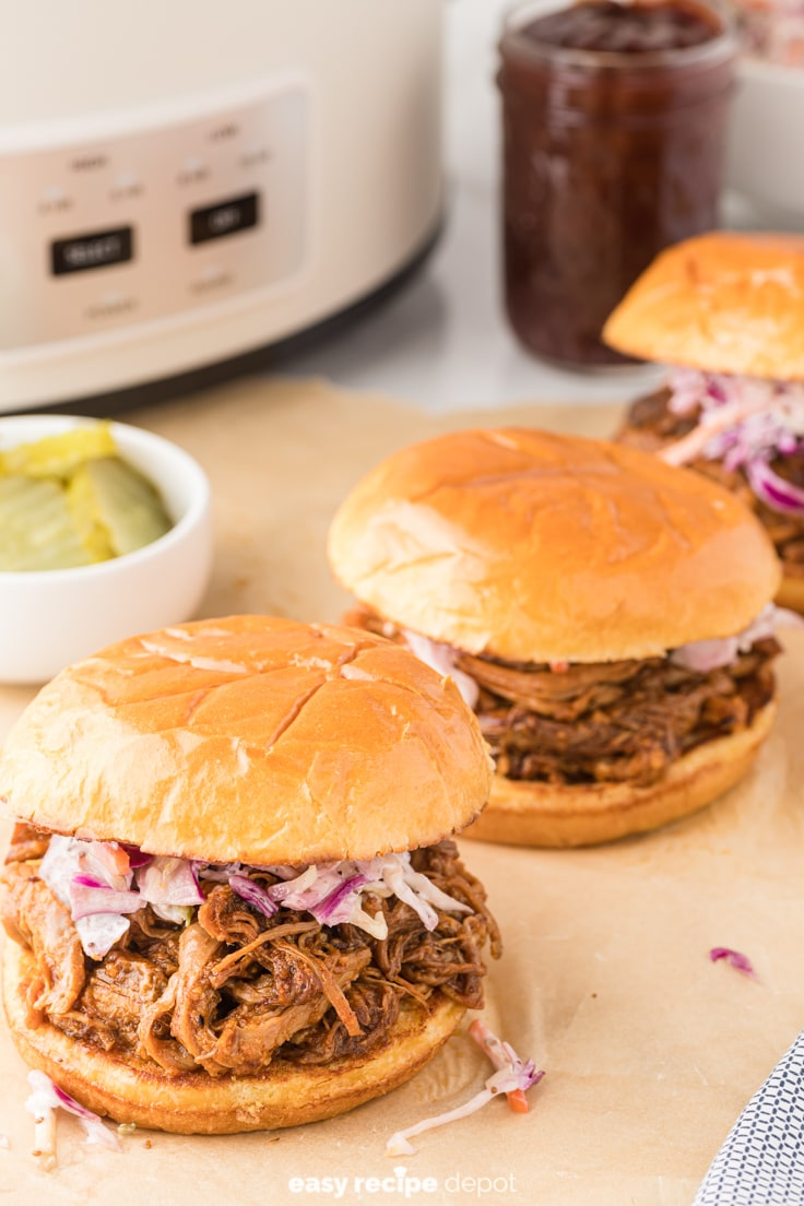 Pulled pork sandwiches in front of a slow cooker.