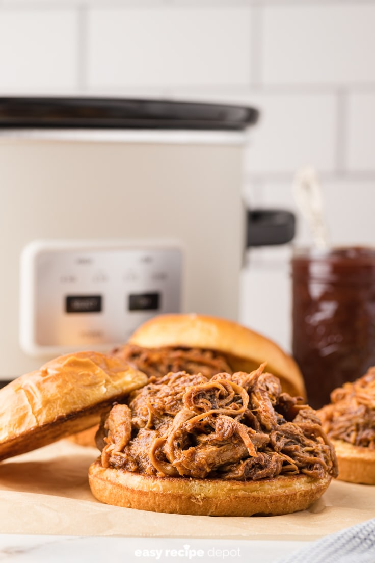 A pulled pork sandwich in front of a Crock Pot.