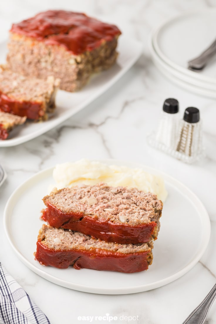 Slices of meatloaf served with mashed potatoes.