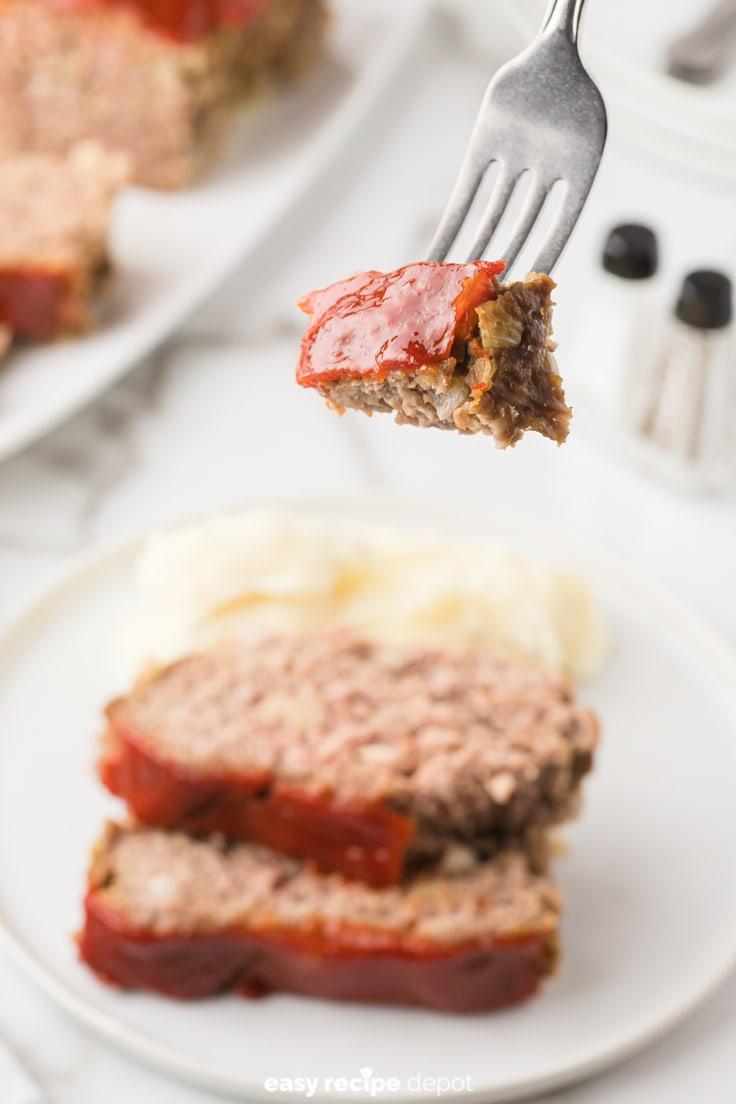 A bite of meatloaf on a fork.