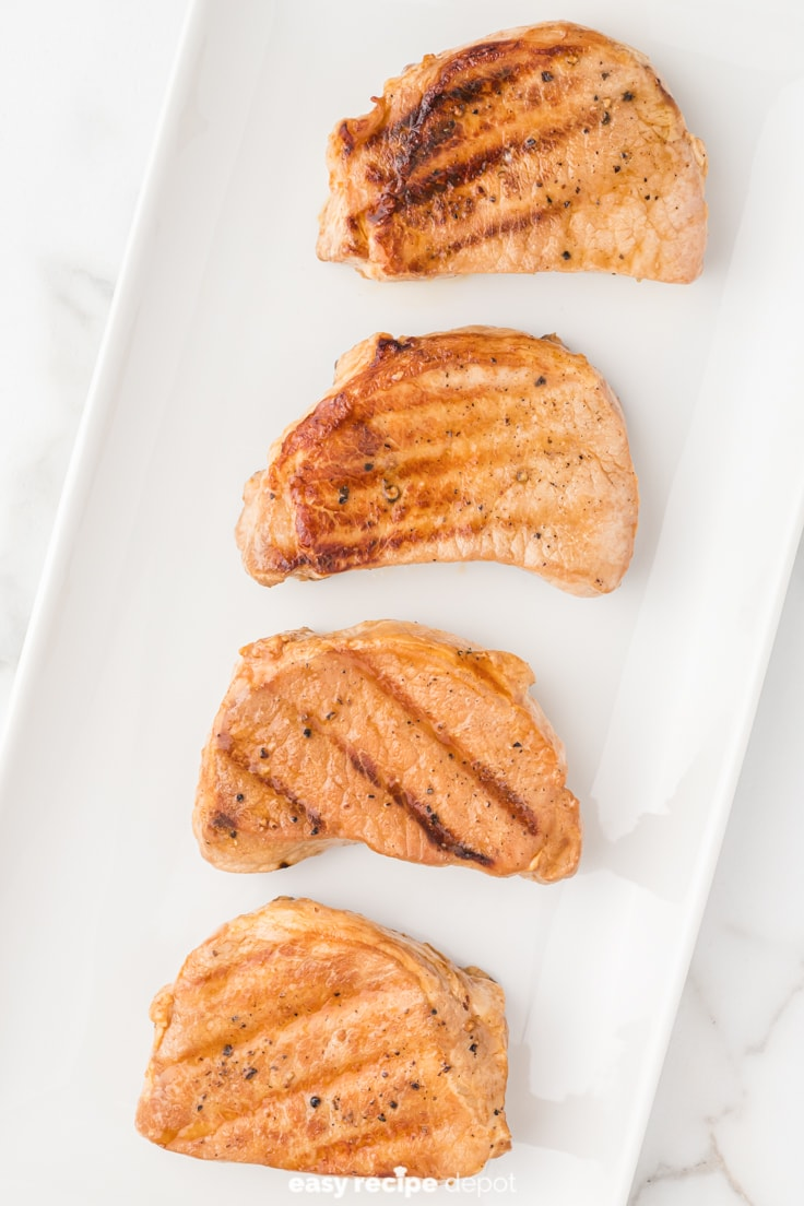 Grilled pork chops on a serving plate.