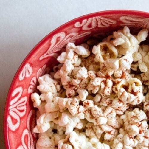 Parmesan popcorn in a red bowl.