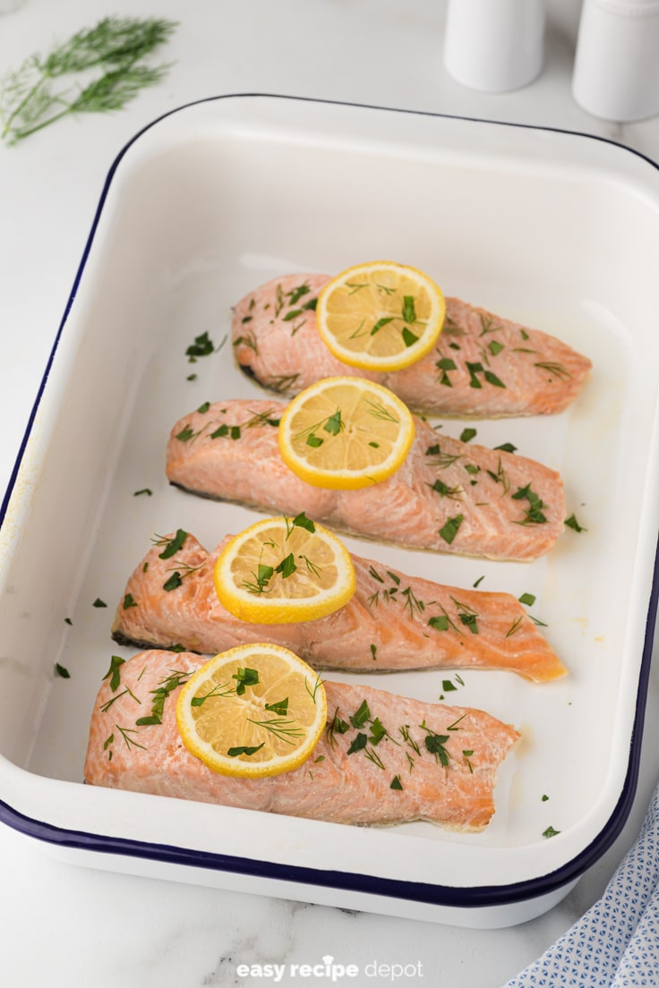 baked salmon from the oven with lemon slices and dill and parsley