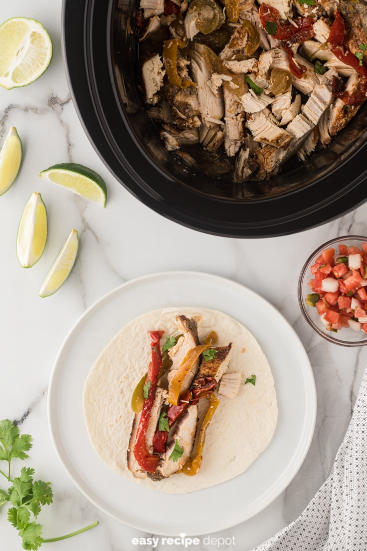Slow cooker chicken fajitas served in a tortilla.